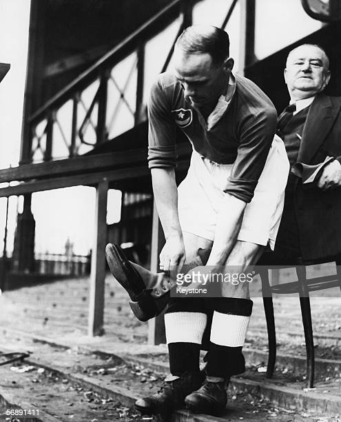 Portsmouth FC manager Jack Tinn has his lucky spats fastened by right winger Freddie Worrall at the Fratton Park ground 4th April 1939 Worrall also...