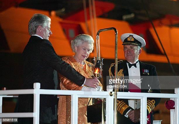The first Sea Lord Admiral Sir Alan West looks on as Bruno Peek helps Britain's Queen Elizabeth II to light the Trafalgar Weekend Beacon during her...
