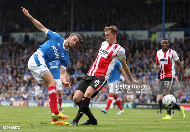 Portsmouth's Christian Burgess gets in a shot ahead of Cheltenham Town's Will Boyle during the Sky Bet League Two match at Fratton Park Portsmouth