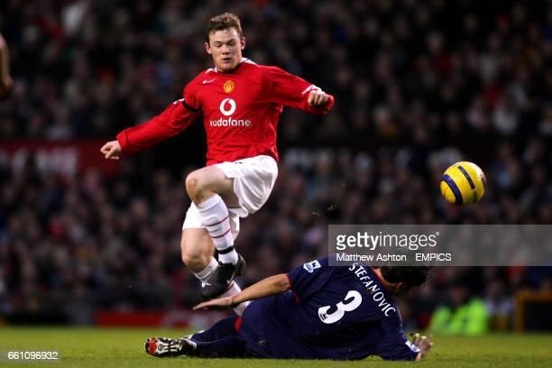 Portsmouth's Dejan Stefanovic slides in on Manchester United's Wayne Rooney