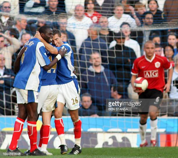 Portsmouth's Djimi Traore and Gary O'Neil celebrate going 20 up against Manchester United after Rio Ferdinand scored an own goal during their...