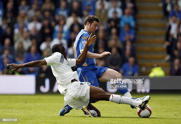 Portsmouth's English Striker David Nugent is tackled by Bolton Wanderers' English midfielder Fabrice Muamba during their Premier League football...