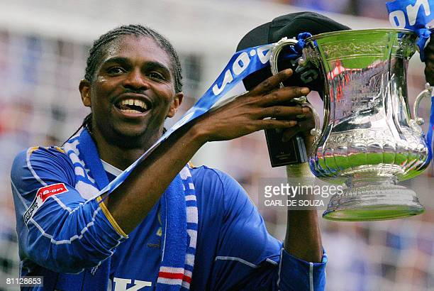 Portsmouth's match goal scorer Nigerian striker Kanu celebrates with the FA Cup trophy after their FA Cup final match against Cardiff City at Wembley...