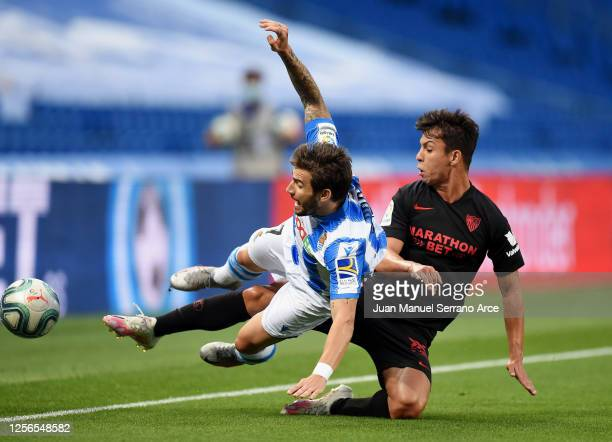 Portu of Real Sociedad is challenged by Oliver Torres of Sevilla during the Liga match between Real Sociedad and Sevilla FC at Estadio Anoeta on July...