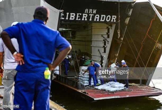 Portuarian employees unload a shipment of humanitarian aid from the Mexican multipurpose vessel Arm Libertador Bal-02 in Havana, on July 30, 2021. -...