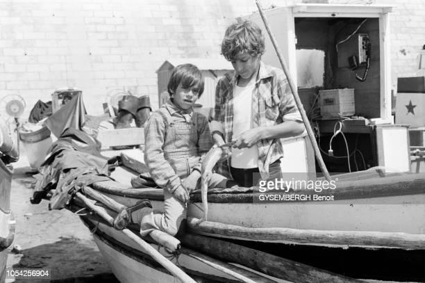 Portugal 1984 Deux jeunes garçons assis sur une barque de pêche à Ericeira L'un deux tenant un couteau s'apprête à ouvrir un poisson