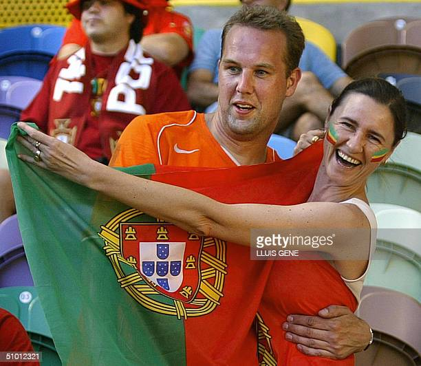 A Portuguese and Dutch fan pose together 30 June 2004 at the Alvalade stadium in Lisbon prior to the Euro2004 semifinal football match between...
