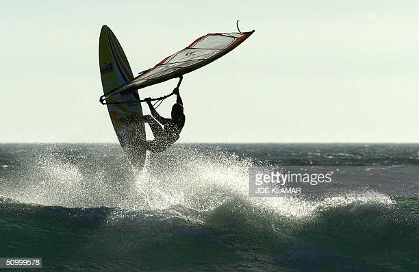 A windsurfer enjoys the wind as he flies over the wave near Cascais beach west of Lisbon 26 June 2004 Cascais is well liked by surfers for its strong...