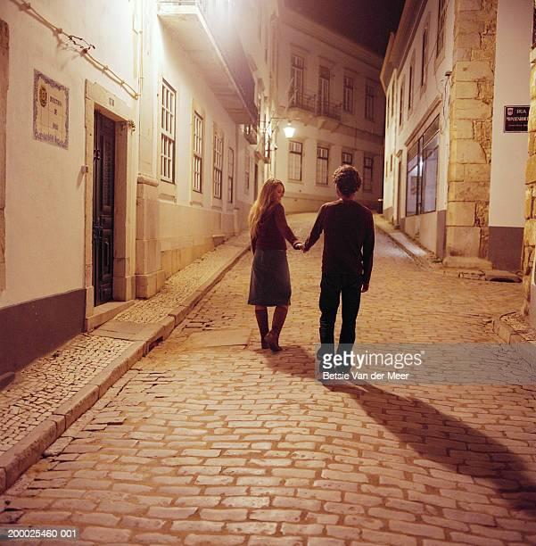Portugal, Algarve, Lagos, couple walking on street at night, rear view