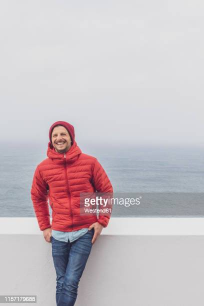 portugal, algarve, sagres, cabo de sao vicente, happy man standing at a wall above the sea - padded jacket stock pictures, royalty-free photos & images