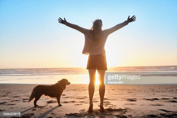 portugal, algarve, woman with dog raising arms on the beach at sunset - arms outstretched stock pictures, royalty-free photos & images