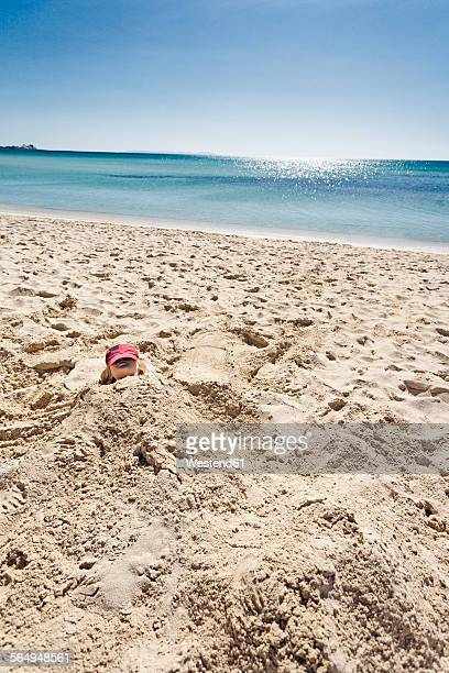 portugal, algarve, young boy with red cap buried in the sandy beach - buried stock pictures, royalty-free photos & images