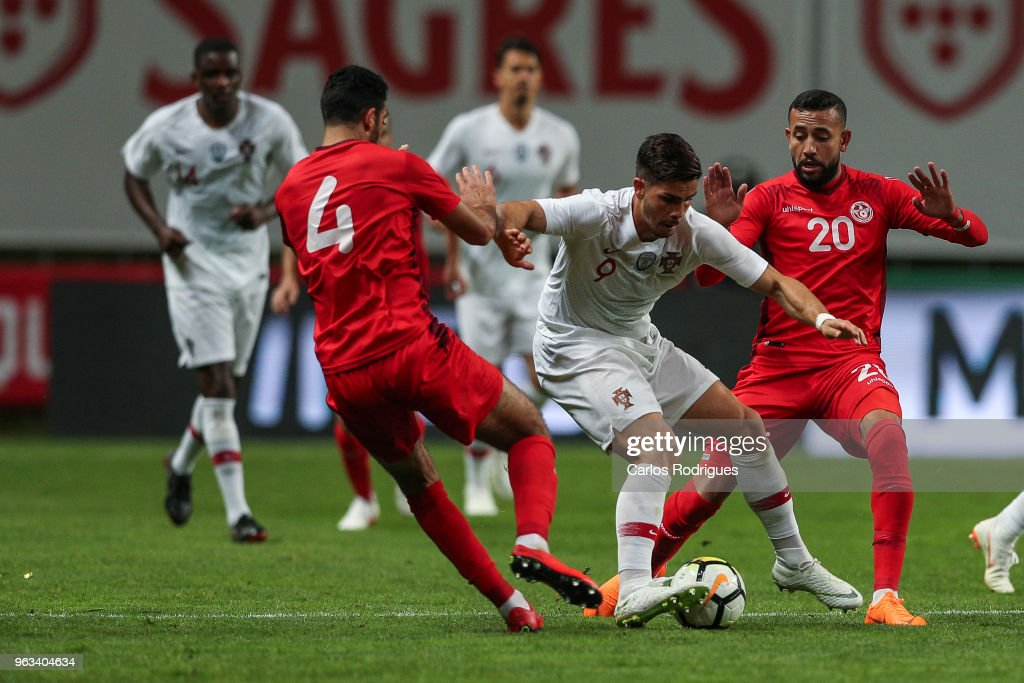 Portugal and AC Milan forward Andre Silva (C) vies with Tunisia defender Yassine Meriah(L) and Tunisia midfielder Ghaylen Chaaleli (R) for the ball possession during the Portugal vs Tunisia International Friendly match on May 28, 2018 in Braga, Portugal.