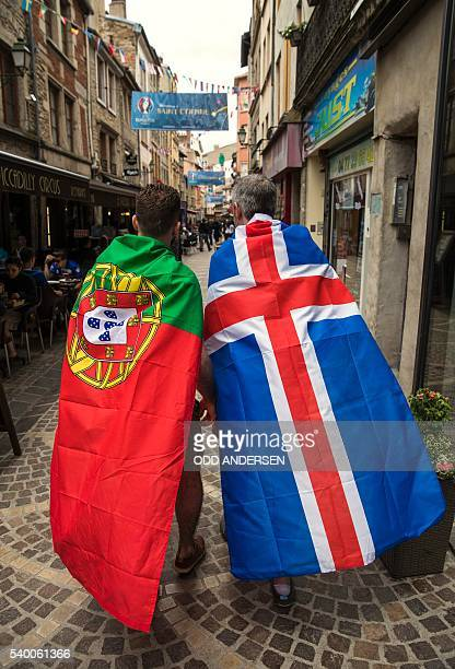 A Portugal and an Iceland supporter walk along a pedestrian street in SaintEtienne on June 14 2016 before the Euro 2016 football match Portugal...