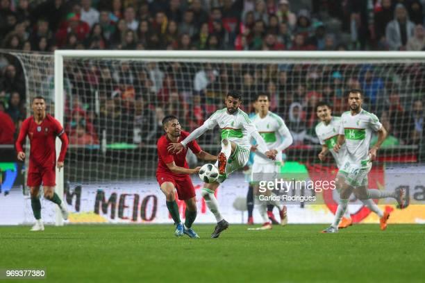 Portugal and Borussia Dortmund defender Raphael Guerreiro vies with Algeria and Leicester City FC forward Riyad Mahrez for the ball possession during...