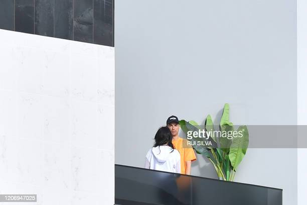 Portugal and Juventus forward Cristiano Ronaldo and his partner Georgina Rodriguez stand on a balcony in Funchal on March 13 2020 Ronaldo has been in...