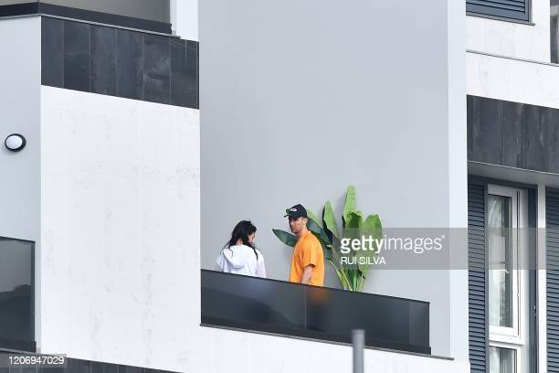 Portugal and Juventus forward Cristiano Ronaldo and his partner Georgina Rodriguez stand on a balcony in Funchal on March 13, 2020. - Ronaldo has...