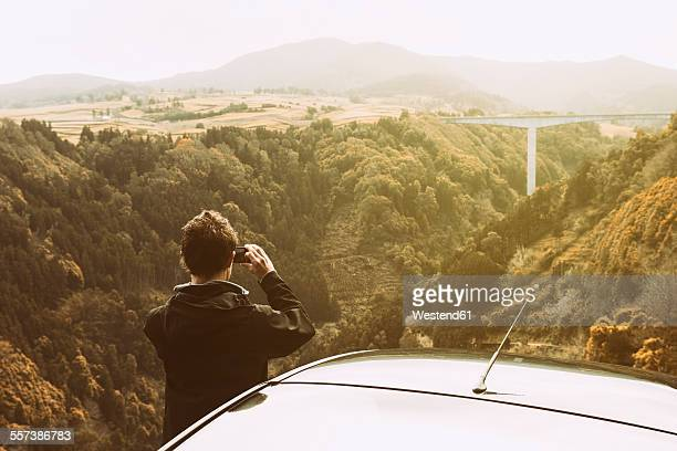 Portugal, Azores, man taking picture of landscape with bridge