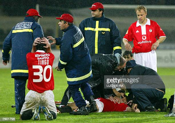 Benfica players Tiago and Andersson watch doctors and medical helps treating Benfica's Hungarian soccer striker Miklos Feher during the Portuguese...