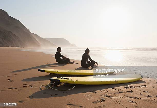 portugal, couple sitting on beach by surfboard - algarve fotografías e imágenes de stock