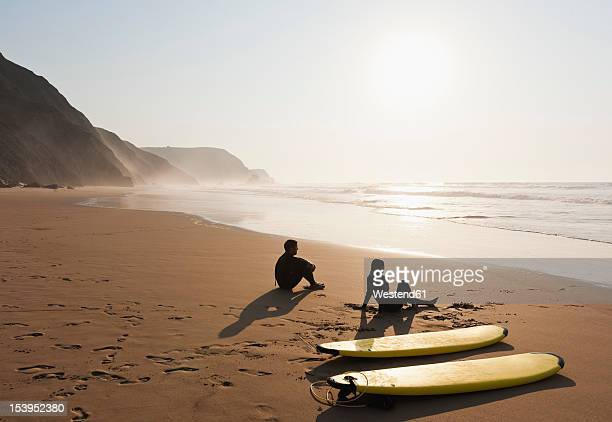 portugal, couple sitting on beach by surfboard - sagres stock pictures, royalty-free photos & images