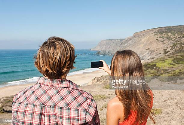 Portugal, Couple taking photograph at beach