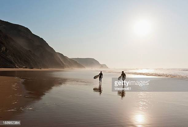portugal, couple walking with surfboard on beach - sagres stock pictures, royalty-free photos & images