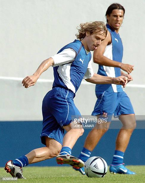 Czech forward Milan Baros watches midfielder Pavel Nedved playing with a ball during a training session in Aveiro during the Euro 2004 22 June 2004....