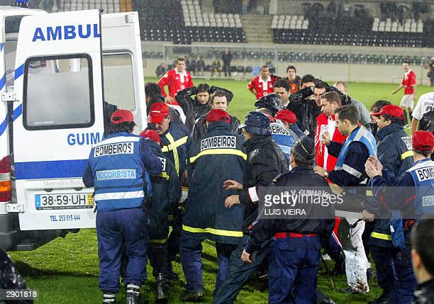 Doctors and medical aides help carrying Benfica's Hungarian soccer striker Miklos Feher during the Portuguese Premier League match held at Guimaraes...