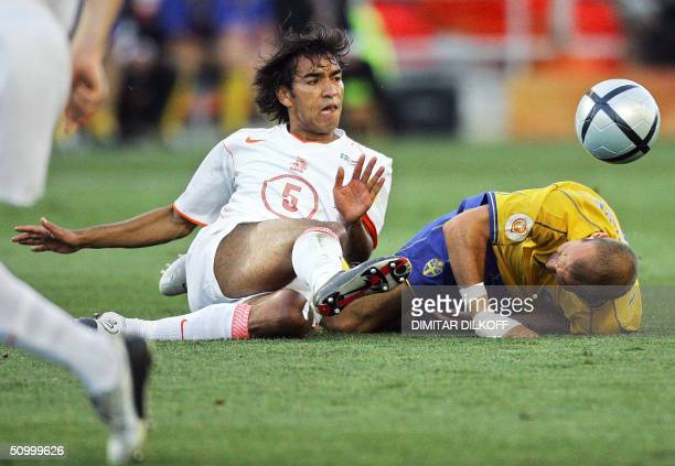 Dutch defender Giovanni Van Bronckhorst vies with Swedish midfielder Fredrik Ljungberg 26 June 2004 at the Algarve stadium in Faro during the Euro...
