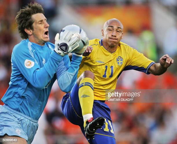 Dutch goalkeeper Edwin Van Der Sar catches the ball in front of Swedish striker Henrik Larsson, 26 June 2004 at the Algarve stadium in Faro, during...