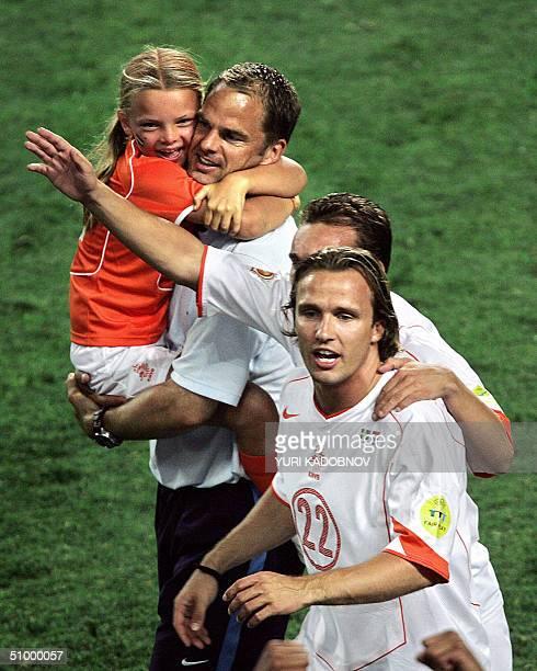 Dutch midfielder Boudewijn Zenden celebrates next to defender Frank De Boer holdin his daughter, 26 June 2004 at the Algarve stadium in Faro, at the...