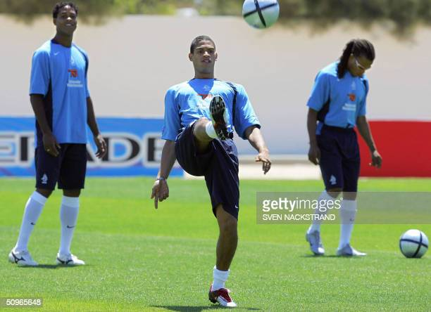 Dutch player Michael Reiziger kicks the ball next to teammates Patrick Kluivert and Edgar Davids during the Dutch training in Albufeira on the...