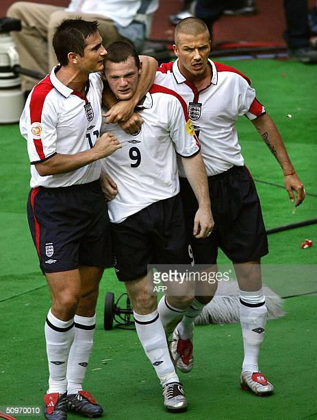 England's midfielder and captain David Beckham and teammate midfielder Frank Lampard congratulate forward Wayne Rooney after his goal 17 June 2004 at...