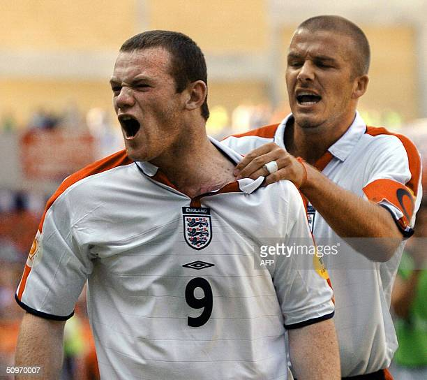 England's midfielder and captain David Beckham congratulates his teammate forward Wayne Rooney after his goal 17 June 2004 at Coimbra's stadium...