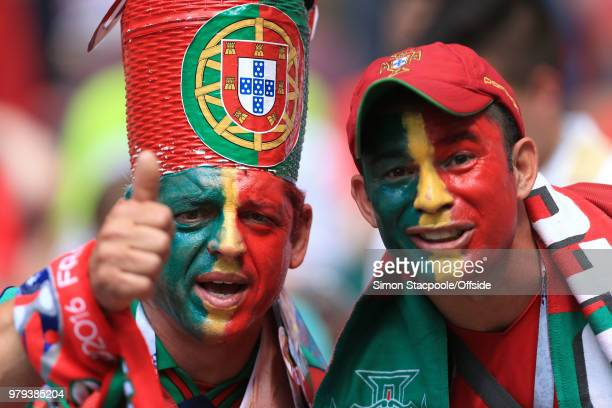 Portugal fans with face paint and hats in the national colours during the 2018 FIFA World Cup Russia group B match between Portugal and Morocco at...