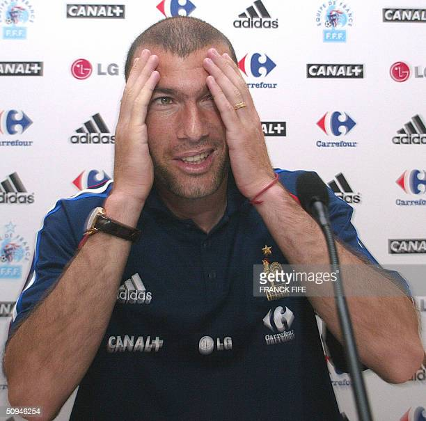 French midfielder Zinedine Zidane gestures as he speaks to journalists during a press conference 10 June 2004 in Santo Tirso some 25 kilometers north...