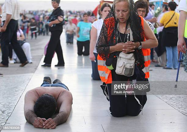 Portugal, Fátima : Pilgrims walk on their knees along the pavement in front of the holy shrine of Fatima, central Portugal on May 12, 2011. Thousands...