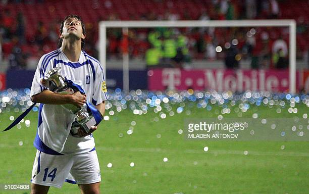Greece's defender Panagiotis Fyssas holds the trophy 04 July 2004 at the Stadio Da Luz in Lisbon after the Euro 2004 final match between Portugal and...