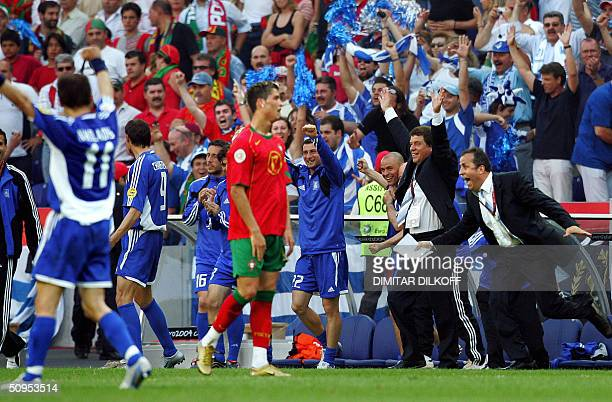 Greece's German head coah Otto Rehhagel raises his arms in victory next to Portugal's forward Cristiano Ronaldo at the end of his team's Euro 2004...