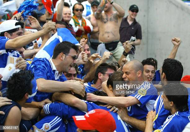 Greece's midfielder Georgios Karagounis is congratulated by teammates and supporters after scoring an opening goal 12 June 2004 at Dragao stadium in...