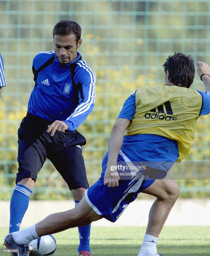 Greece's striker Demis Nikolaidis vies for the ball with