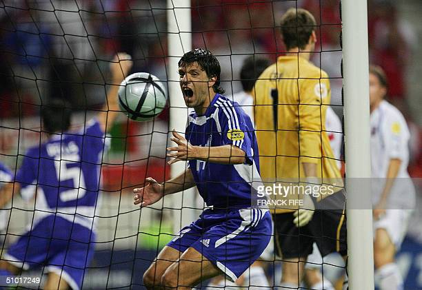 Greek defender Traianos Dellas celebrates his winning goal next to Greek defender Panagiotis Fyssas, 01 July 2004 at Dragao stadium in Porto, during...