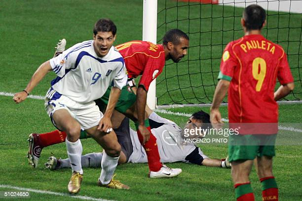 Greek forward Angelos Charisteas celebrates his opening goal next to Portuguese midfielder Costinha and goalkeeper Ricardo 04 July 2004 at the Luz...