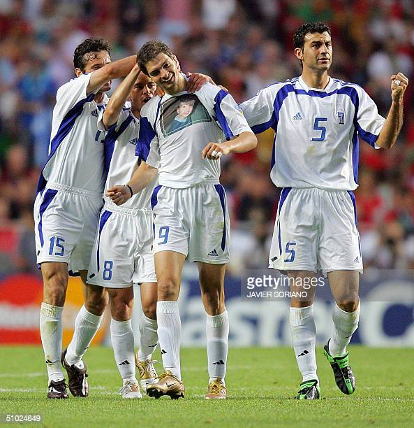 Greek forward Angelos Charisteas is congratulated by his teammates after scoring the opening goal for his team, 04 July 2004 at the Luz stadium in...