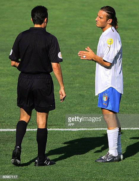 Italy's forward Francesco Totti speaks with the referee Manuel Enrique Mejuto Gonzalez 14 June 2004 at Henriques stadium in Guimaraes during the...
