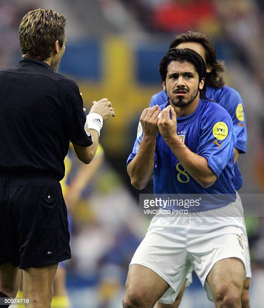 Italy's midfielder Gennaro Gattuso chats with Swiss referee Urs Meier 18 June 2004 at the Dragao stadium in Porto during their Euro 2004 Group C...