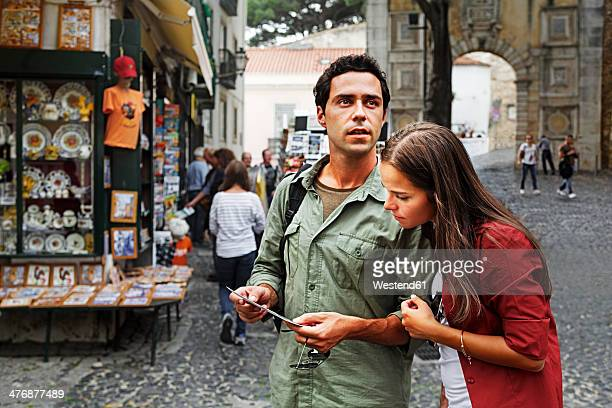 Portugal, Lisboa, Baixa, Rossio, young couple looking at postcard