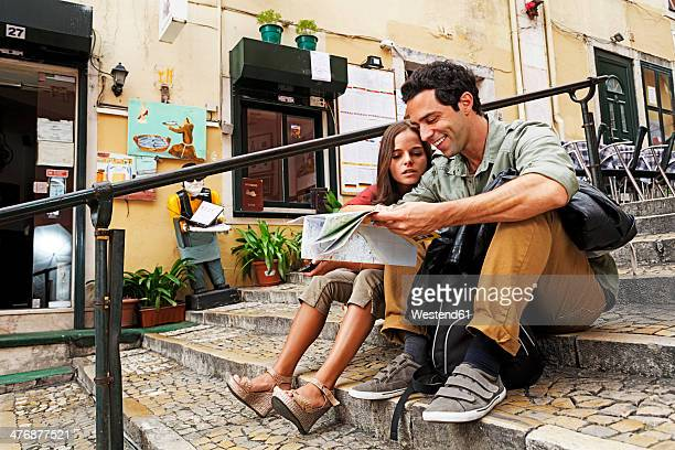 Portugal, Lisboa, Carmo, Calcada du Duque, young couple with city map sitting at stairs