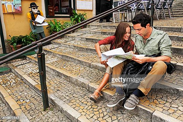 Portugal, Lisboa, Carmo, Calcada du Duque, young couple with city map sitting on stairs